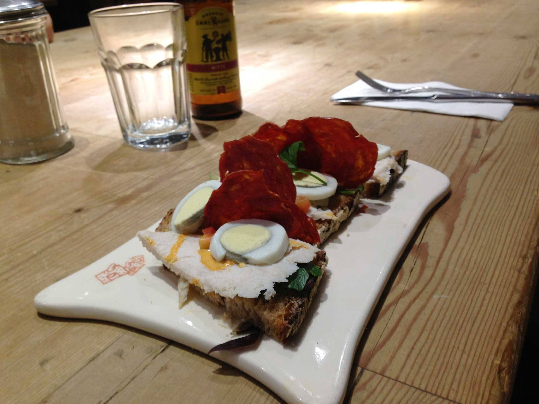 An open faced sandwich with slices of chicken and egg