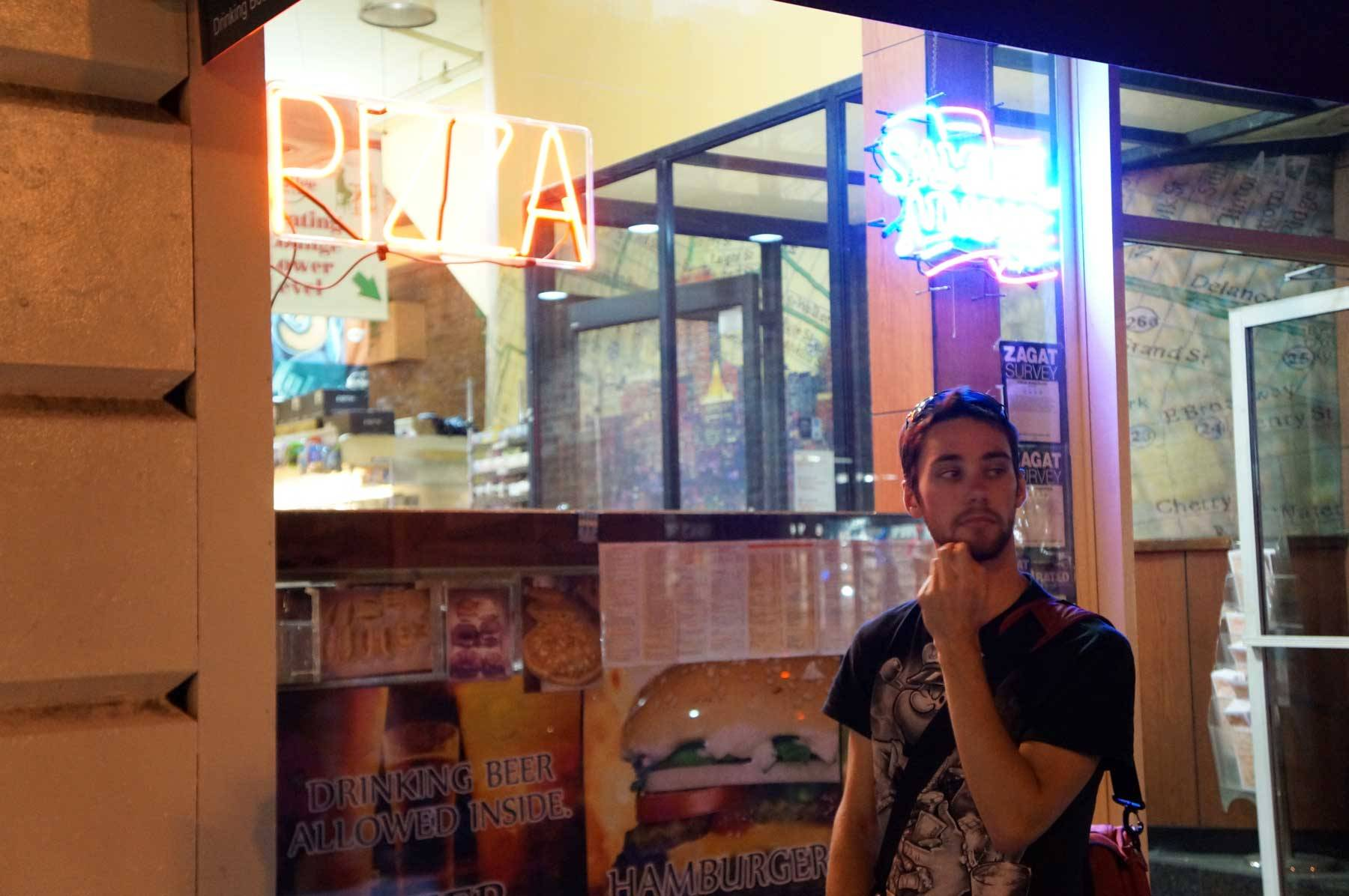 "Jared outside a building with the sign ""Pizza"""