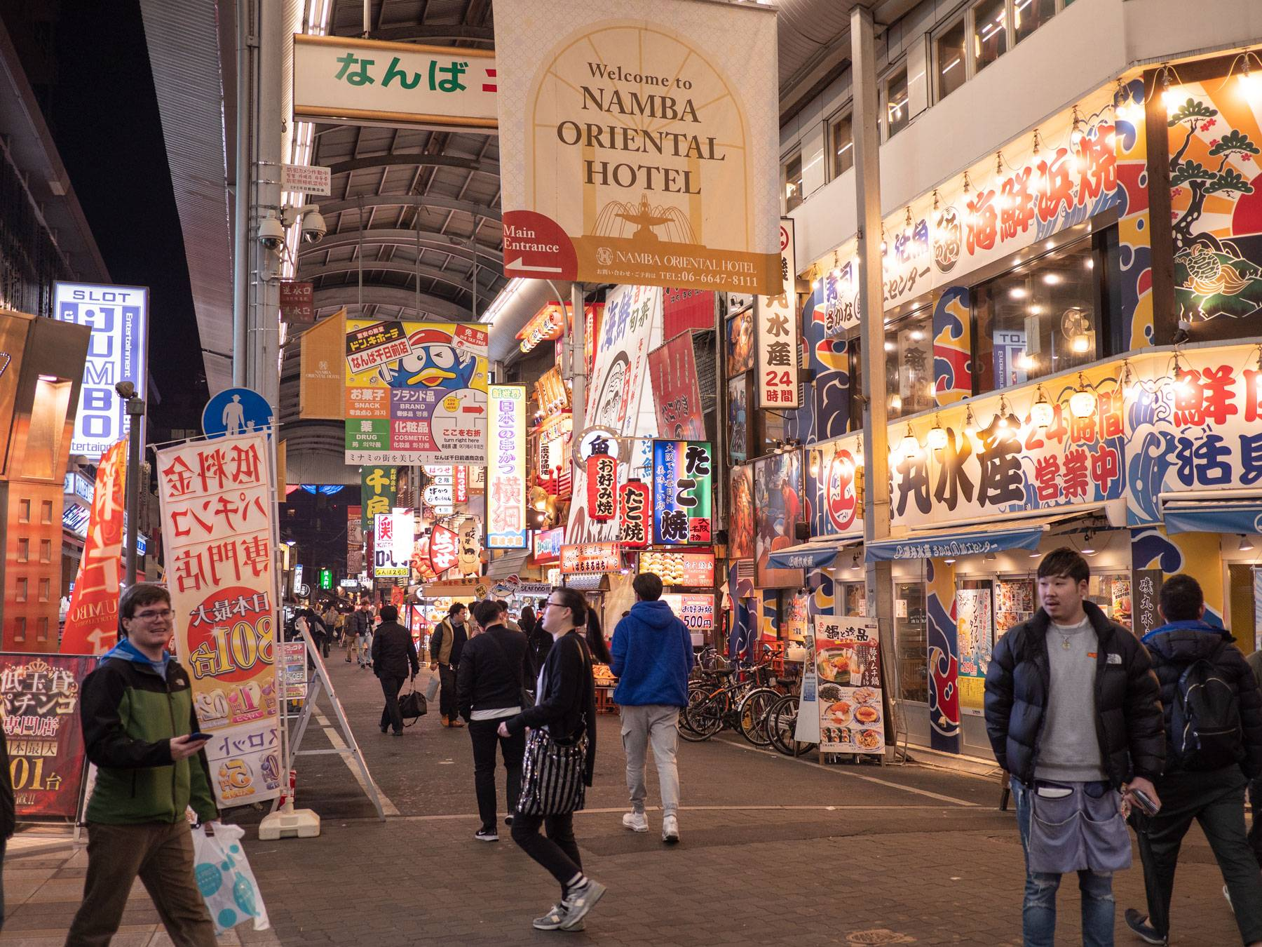 A crowd of people in a Dōtonbori shopping alley